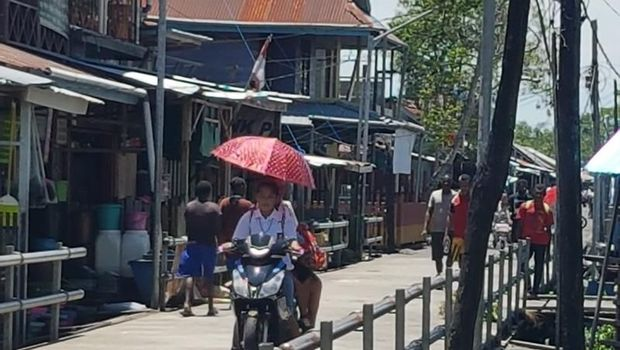 Warga Agats, ibu kota Kabupaten Asmat memakai motor listrik