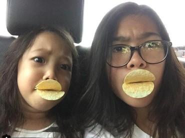 Memanfaatkan keripik untuk pasang eskpresi duckface bareng si kakak. Ada-ada aja deh tingkahmu, Jenaka. (Foto: Instagram/ @jenaka_sudiro)
