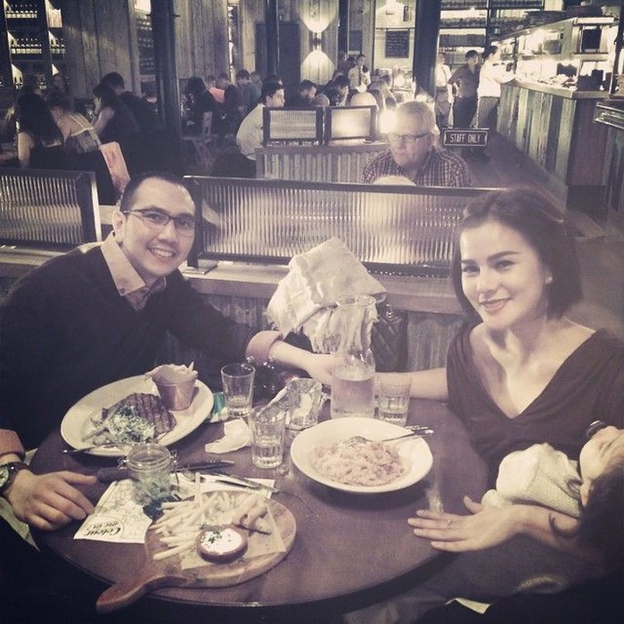 So sweet! Tangan kanan Astrid berpegangan dengan tangan sang suami, terus tangan kirinya menopang anaknya yang lagi tidur. Saat itu mereka makan malam dengan steak dan pasta. Foto: Instagram Astrid Tiar