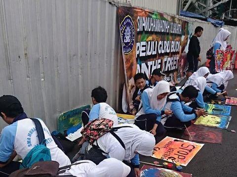 Para siswa melukis untuk aksi solidaritas Guru Budi