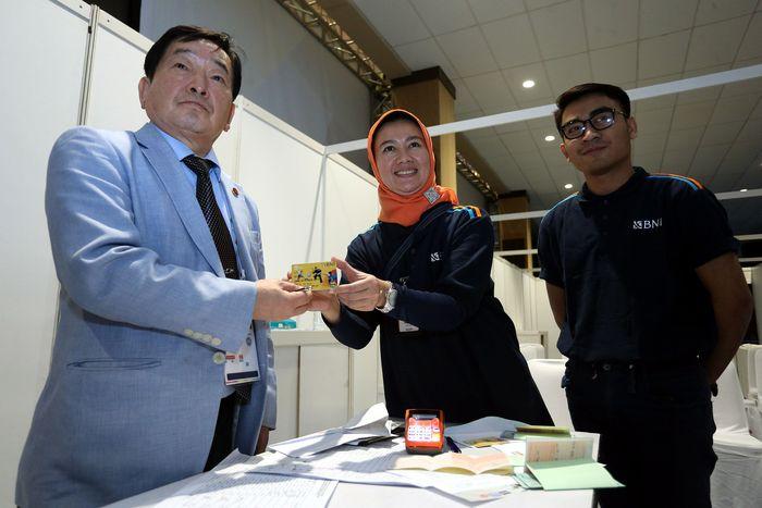 Salah seorang ITO (International Technical Officer) yang berasal dari Korea (kiri) menerima Kartu BNI Virtual Account Debit di Jakarta (11/2/2018). Pool/BNI.