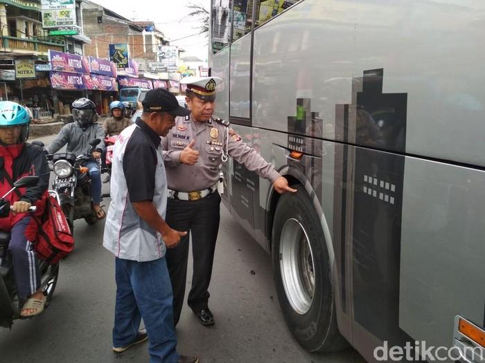 Polisi memeriksa kelaikan bus pariwisata di kawasan Bundaran STM, Tarkal, Kabupaten Garut. (Foto: Hakim Ghani/detikcom)