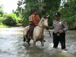 Dengan Kudanya, Polisi Ini Bantu Siswa Seberangi Sungai