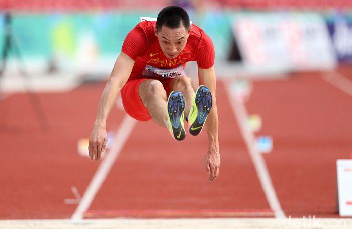 Atlet lompat jauh China Yaoguang Zhang melakukan lompatan.