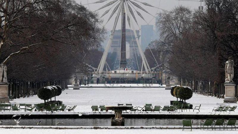 Selain Menara Eiffel, sejumlah landmark lain seperti Tuileries Garden dan bianglala di dekatnya juga ikut tertutup salju (Reuters)