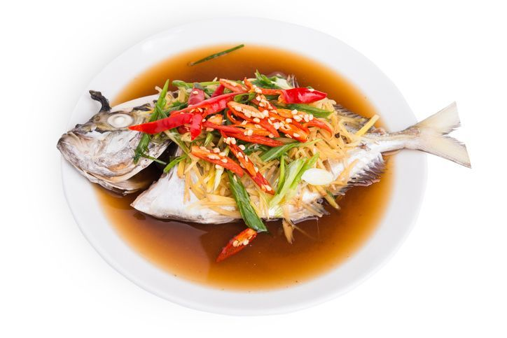 Chinese Food whole fish steamed with ginger, scallion and soy sauce, served on a platter with head and tail complete.