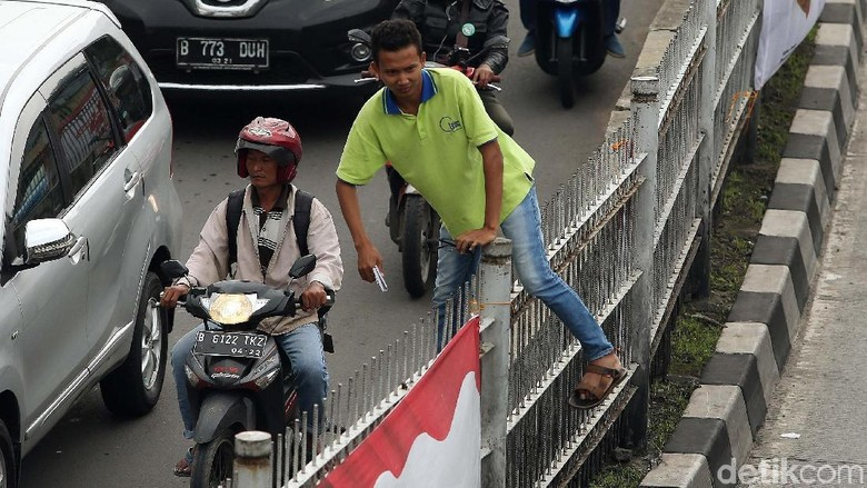 Aksi Nekat Penyeberang Naik Pagar Tinggi di Jatinegara
