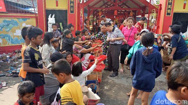 Warga Tionghoa tersenyum sambil bagi-bagi angpao.