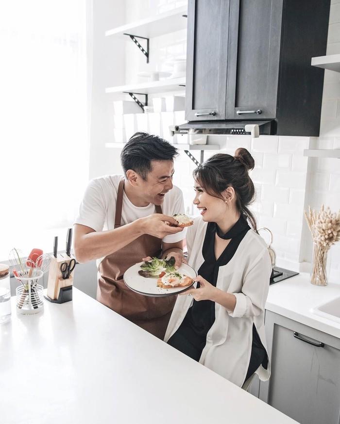 Bersama istrinya, Fiona Anthony, ia asyik makan sandwich bersama. Dion yang masih mengenakan celemek, terlihat menyuapi sang istri. Romantis ya? Foto: Instagram @dionwiyoko