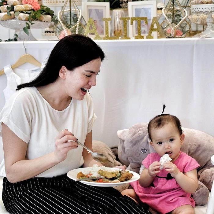 Foto yang diposting ke akun instagaram @alicenorin ini menunjukkan kedekatannya dengan buah hati. Si kecil Alita asyik makan kerupuk sementara Alice memegang piring berisi nasi lengkap. Foto: Instagram @alicenorin