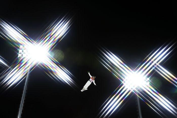 David Morris (Australia) melayang di udara di antara dua lampu penerang saat melakukan latihan pada nomor ski gaya bebas di Phoenix Snow Park (Photo by Cameron Spencer/Getty Images)