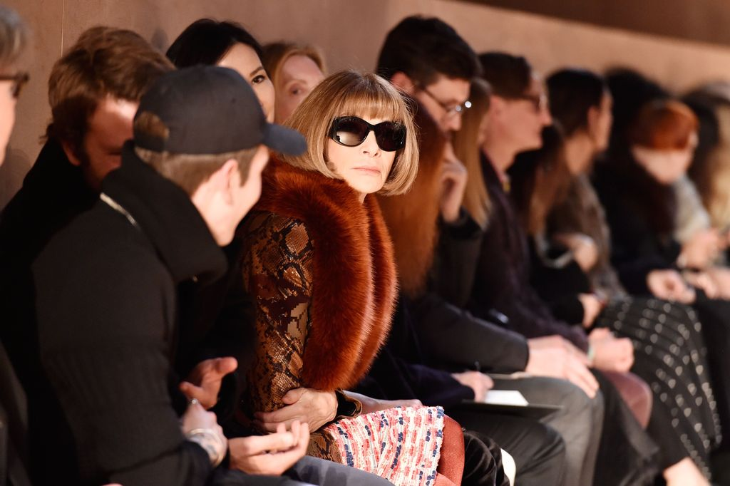 LONDON, ENGLAND - FEBRUARY 20:  Queen Elizabeth II sits next to Anna Wintour (R) and Caroline Rush, chief executive of the British Fashion Council (BFC) (L) as they view Richard Quinn's runway show before presenting him with the inaugural Queen Elizabeth II Award for British Design as she visits London Fashion Week's BFC Show Space on February 20, 2018 in London, United Kingdom. (Photo by Yui Mok - Pool/Getty Images)