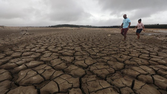 A family negotiates their way through caked mud around a dried up section of the Theewaterskloof dam near Cape Town, South Africa, January 20, 2018. The dam, which supplies most of Cape Towns potable water, is currently dangerously low as the city faces Day Zero, the point at which taps will be shut down accross the city.  Picture taken January 20, 2018. REUTERS/Mike Hutchings
