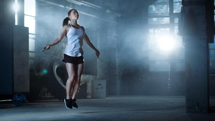Athletic Beautiful Woman Exercises with Jump / Skipping Rope in a Gym. Shes Covered in Sweat from Her Intense Cross Fitness Training. Dark atmosphere.
