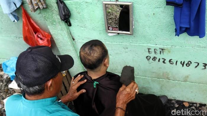 Sudah puluhan tahun Pak Ebit menjadi tukang cukur. Dia biasanya mangkal di pingkir rel kereta api di kawasan Roxy, Jakarta.