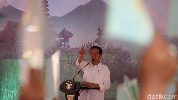 Presiden Jokowi saat membagikan sertifikat tanah.