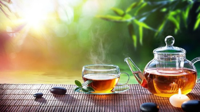 Cup of tea, mint leaves, lemon slices and brown sugar