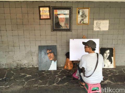 Jaya, pelukis jalanan di trotoar kawasan Kota Tua, Jakarta.