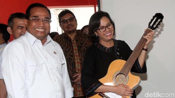 Menteri Keuangan Sri Mulyani dan Menteri Perhubungan Budi Karya Sumadi melihat koleksi yang bakal dilelang di Galeri Nasional, Jakarta, Rabu (28/2/2018). Ia tampak semringah.