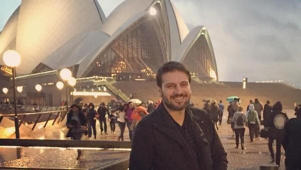 Dengan wajah tampan dan senyum memikat, Sami berfoto dengan Gedung Opera Sydney yang terkenal. (samiyusuf/Instagram)