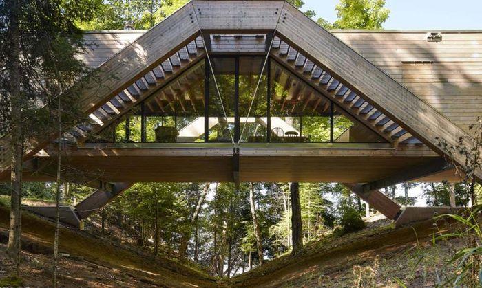 Rumah ini berdiri di tengah hutan dengan dikelilingi berbagai pepohonan. Bagian depan rumah menghadap ke danau dan menciptakan perasaan seperti berada di antara puncak pohon. Istimewa/Inhabitat