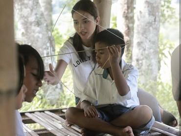 Dengan sabar mengajari anak-anak membuat layang-layang. (Foto: Instagram @putrimarino/ @taufanadryan)