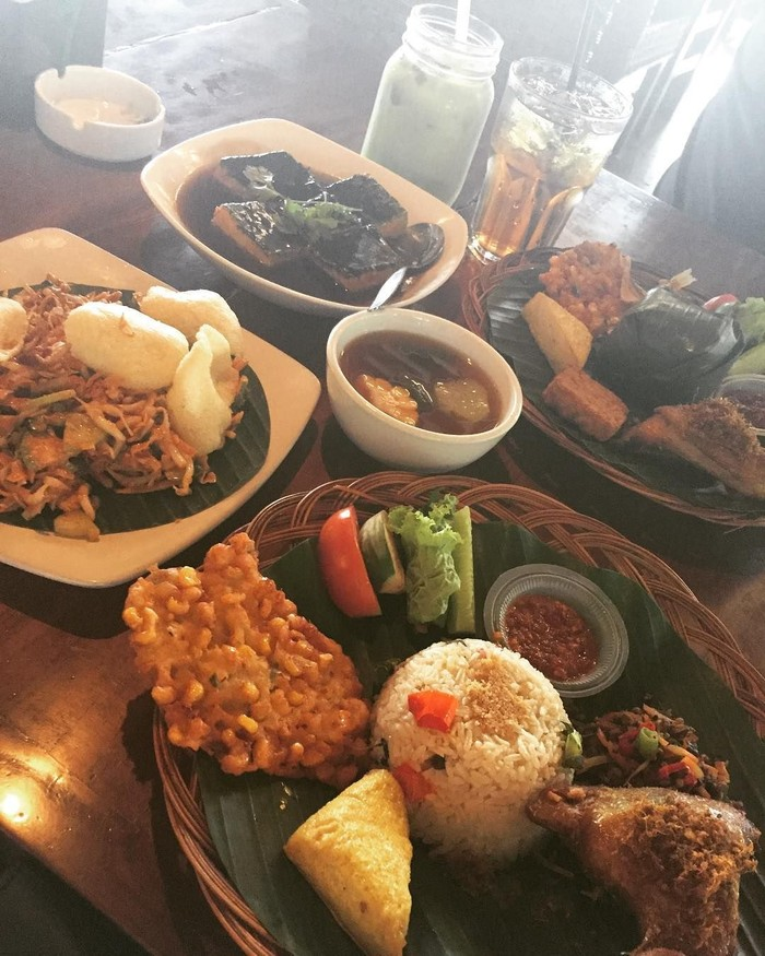 Beralaskan daun pisang, nasi timbel disajikan bersama ayam goreng, bakwan jagung, tahu, sambal, serta karedok dan sayur asam pilihan @ayeshasoedrajat86 di Dleuit Bogor. Foto: Instagram/Istimewa