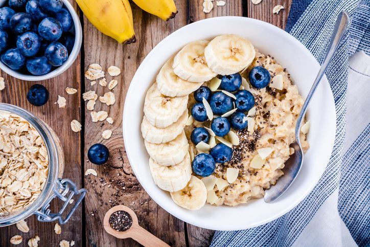 Bowl of homemade oatmeal porridge with banana, blueberries, almonds, coconut and caramel sauce on teal rustic table from above, hot and healthy food for Breakfast