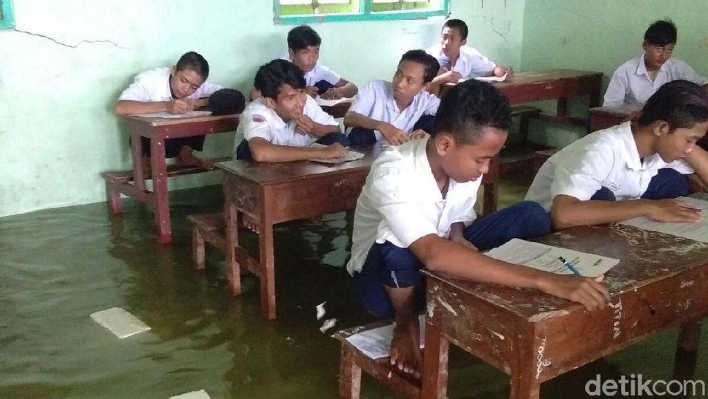 Foto: Siswa MTs Nangkring di Kursi saat Ujian karena Banjir