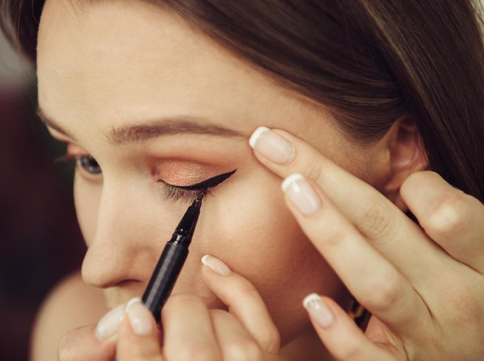 Woman doing makeup and painting black arrows