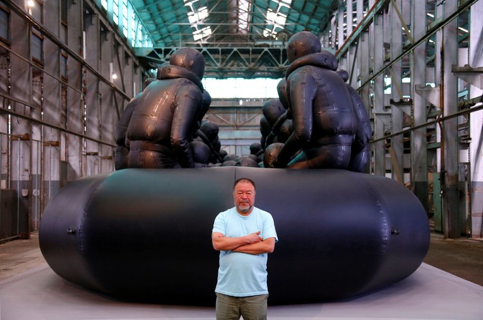 Chinese artist Ai Weiwei stands in front of his artwork consisting of a 60-metre rubber raft installation titled 'Law of the Journey' which includes around 300 figures representing refugees, during a media call for the Biennale of Sydney located in the industrial precinct of Cockatoo Island in Australia, March 12, 2018.   REUTERS/David Gray   NO RESALES NO ARCHIVE