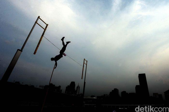 Atlet lompat galah beraksi.