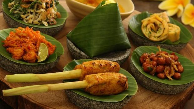 Assorted popular Balinese dishes commonly offered in Nasi Campur Bali, now served in individual portion. Each dish is plated on a mini stoneware mortar lined with banana leaf; while the curry soup is in a small bowl. The dishes are (in clockwise direction): Sate Lilit (minced seafood satay), Ayam Pelalah (shredded chicken in red chili paste), Jukut Urap (vegetable salad with coconut dressing), Jukut Gedang Mekuah (green papaya curry),  Telur Dadar (egg omelet), Kacang Teri (fried peanuts and anchovies) and Nasi Kuning (turmeric rice) in the center.