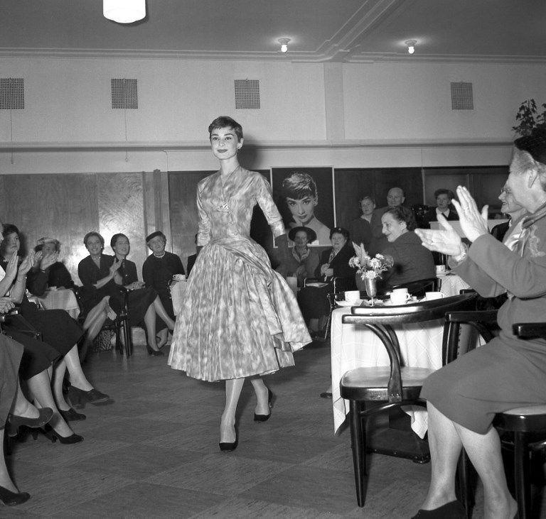 L'actrice Audrey Hepburn présente une création du couturier Hubert de Givenchy, lors d'un défilé de mode, en novembre 1954, à Amsterdam.Actress Audrey Hepburn shows a Givenchy model, during a fashion show, in November 1954, in Amsterdam. / AFP PHOTO