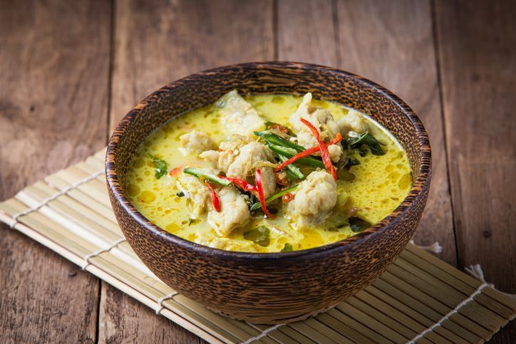 Hot and spicy pork green curry on a wood table