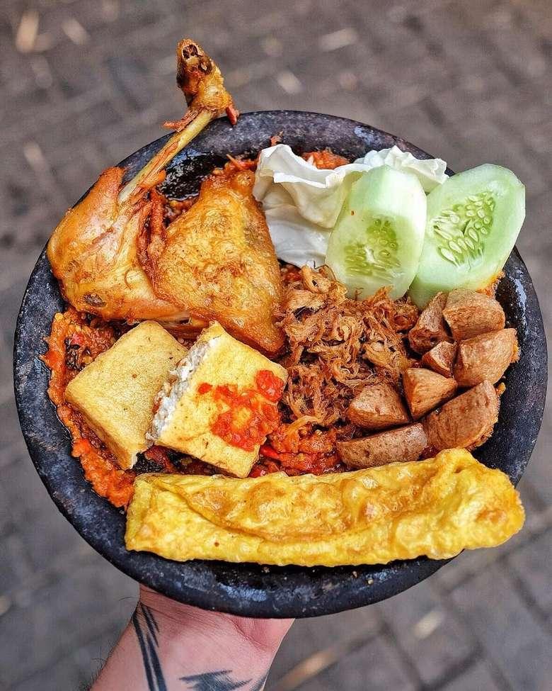 @Henjiwong memilih makan siang ayam goreng penyet paket komplet di Warung Bu Kris. Selain ayam, ada empal, telur dadar, tahu, tempe, dan bakso goreng. Disajikan diatas cobek dan sambal pedas yang sedap. Foto: Instagram