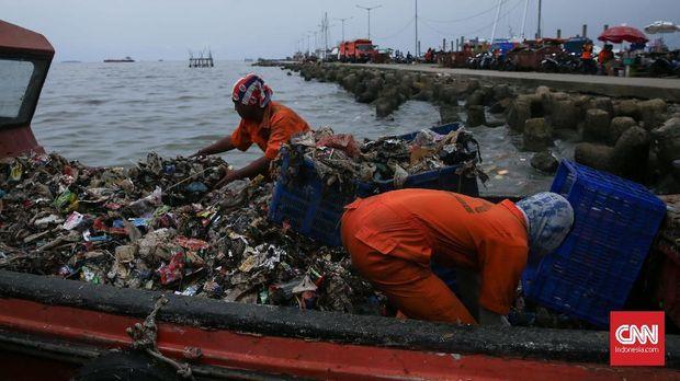 Petugas mengangkut timbunan sampah dari Muara Angke, Jakarta Utara, Senin (19/3).