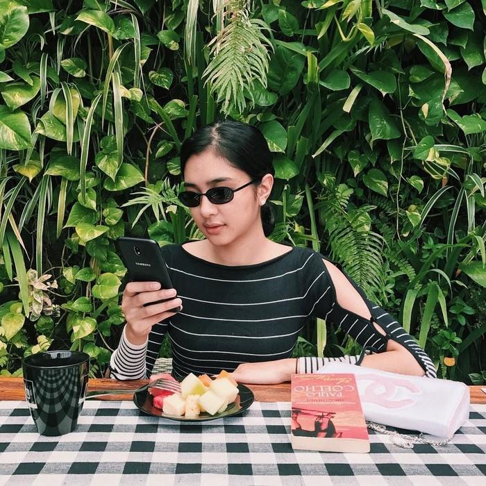 Memiliki tubuh yang langsing dan tinggi semampai. Ternyata Mikha juga gemar makan buah lho. Tuh lihat, dimejanya ada sepiring potongan buah yang tampak segar. Foto: Instagram @miktambayong