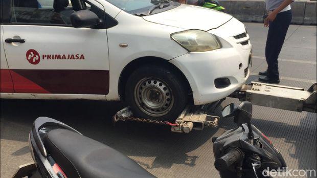 Sopir taksi hanya bisa pasrah saat mobilnya diderek petugas
