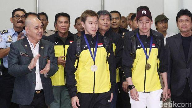 Herry Iman Pierngadi di antara Kevin/Marcus saat tiba di bandara Soekarno Hatta.