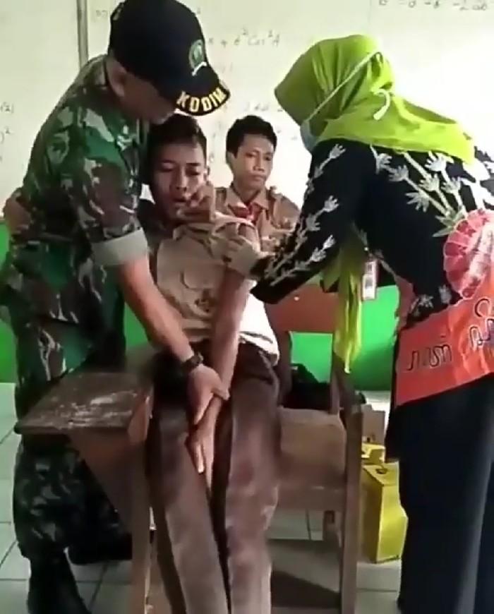 Jarum suntik pun akhirnya mendekat ke lengan siswa tersebut. Foto: Instagram