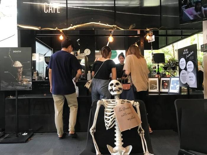 Kid-Mai Death Cafe berlokasi di 1191 Soi Ari 1, Khwaeng Samsen Nai, Bangkok. Masuk ke kafe ini, kamu langsung disuguhi interior serba hitam dan bahkan ada rangka tengkorak dibiarkan duduk. Hiii... Foto: Facebook Kid-Mai Death Cafe