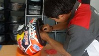 Di seri MotoGP Qatar akhir pekan kemarin, Mugi menyalurkan jasanya dalam mengurusi helm Andrea Dovizioso. Helm yang digunakan oleh Dovizioso adalah merek Suomy.Foto: Facebook/Nathania Mugiyono