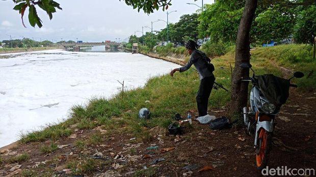Meski dipenuhi busa di bagian permukaan, masih ada orang yang memancing di lokasi tersebut