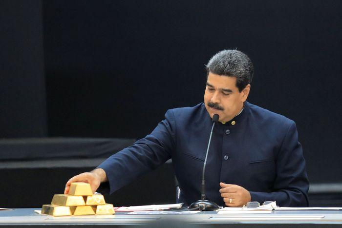 Presiden Venezuela Nicolas Maduro memegang emas batangan saat rapat para menteri ekonomi di Istana Miraflores di Caracas, Venezuela, Kamis (22/3) waktu setempat. REUTERS/Marco Bello.
