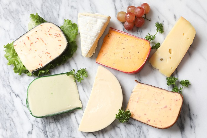 An overhead close up horizontal photograph of four artisanal and three traditional cheeses. Jalapeño peppadew,brie, buffalo wing flavor, Jarlsberg, smoked Gouda with bacon, sharp Provolone and Wasabi (horseradish) flavored cheese, garnished with curly parsley and some red grapes.
