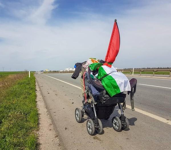 Benjamin berjalan kaki dengan sebuah stroller bayi berisi kebutuhannya (walktopalestine/Instagram)