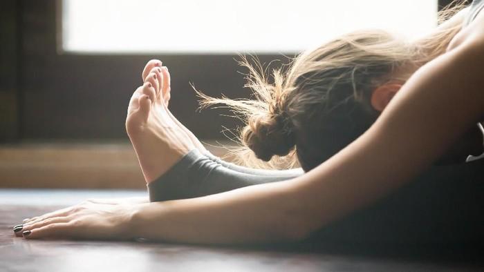 Young woman doing yoga twisting mat indoors near window