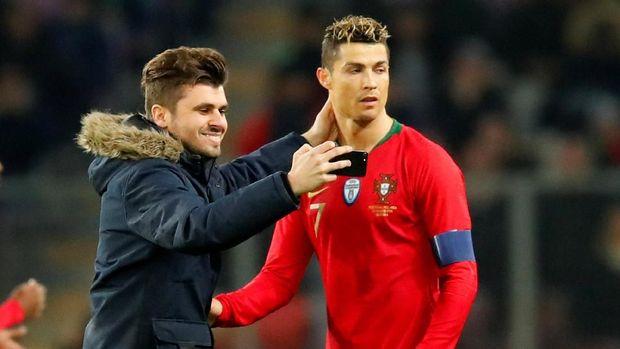 Seorang penonton yang masuk ke dalam lapangan saat pertandingan Portugal vs Belanda berfoto dengan Cristiano Ronaldo.