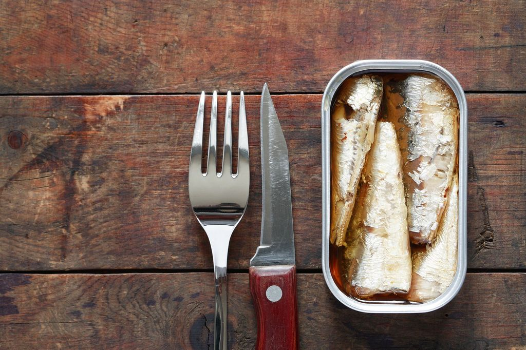 Open canned fish near fork and knife on wooden background with free space